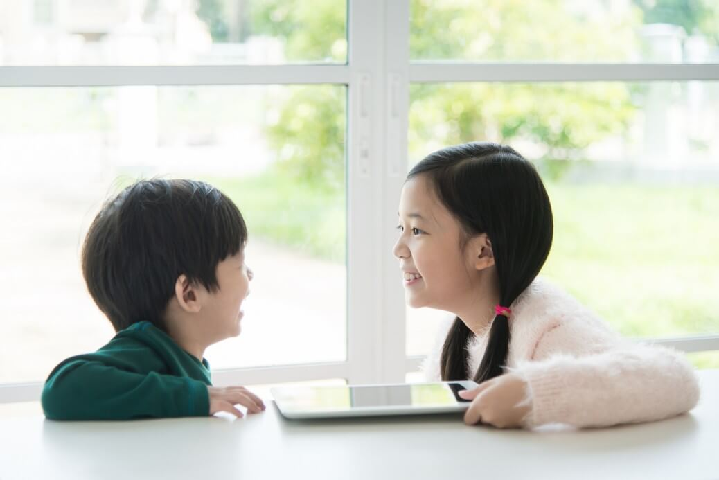 Portrait of happy asian children with tablet on white table